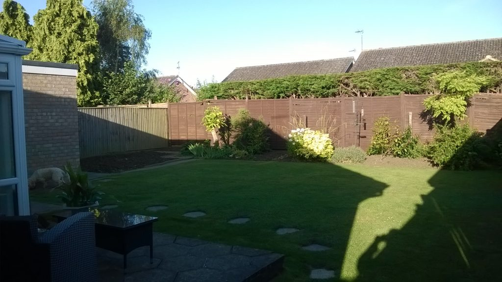 the garden before landscaping, lawn from fence to fence and a flower bed along the rear.