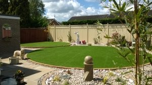 an image of circular lawns made with artificial grass as part of a new garden design included cobble covered flower beds